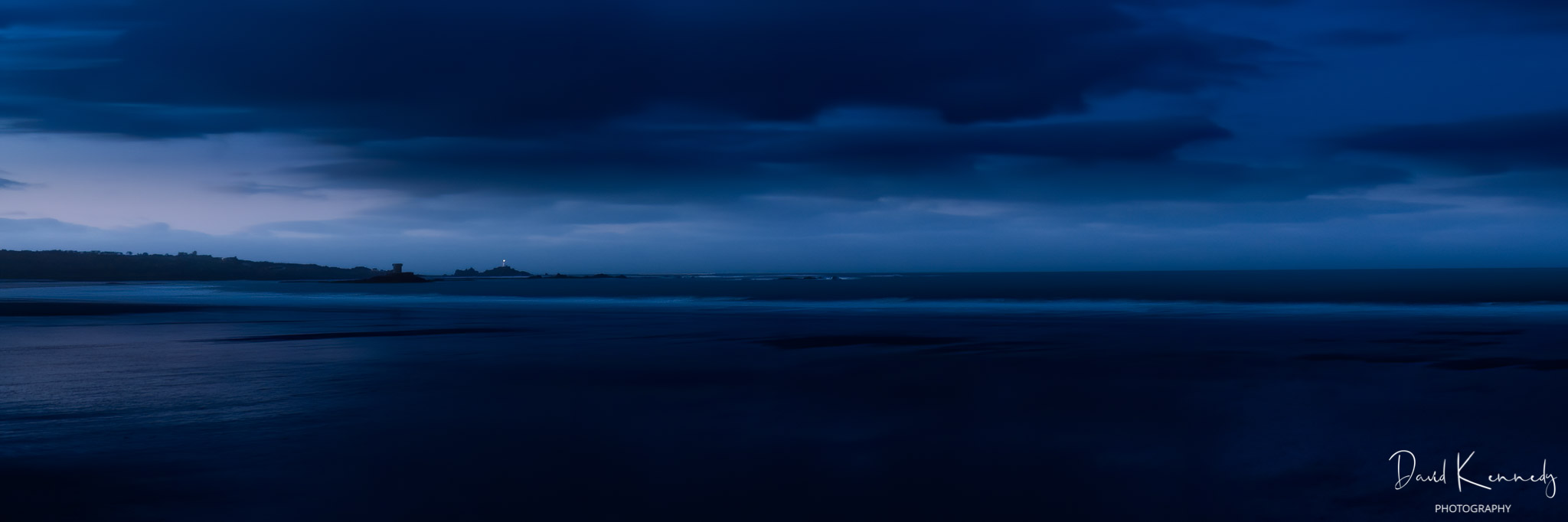 View over beach and sea in the blue hour with Lighthouse