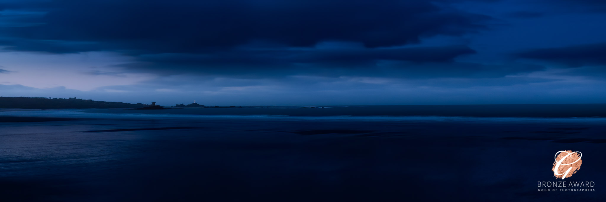 Blue hour vista taken before dawn showing Corbiére Lighthouse shining, and deep blue beach and sky at St Ouen's