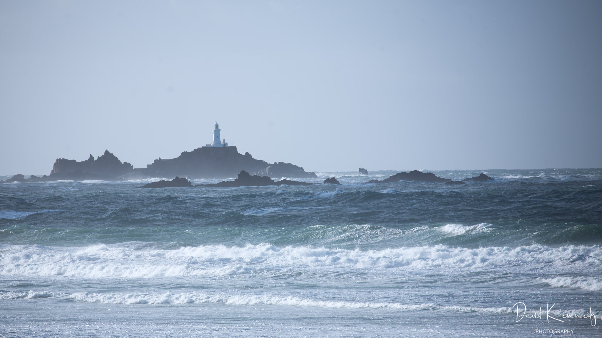 On a windy day, the waves break on the beach and on the rocks around the lighthouse