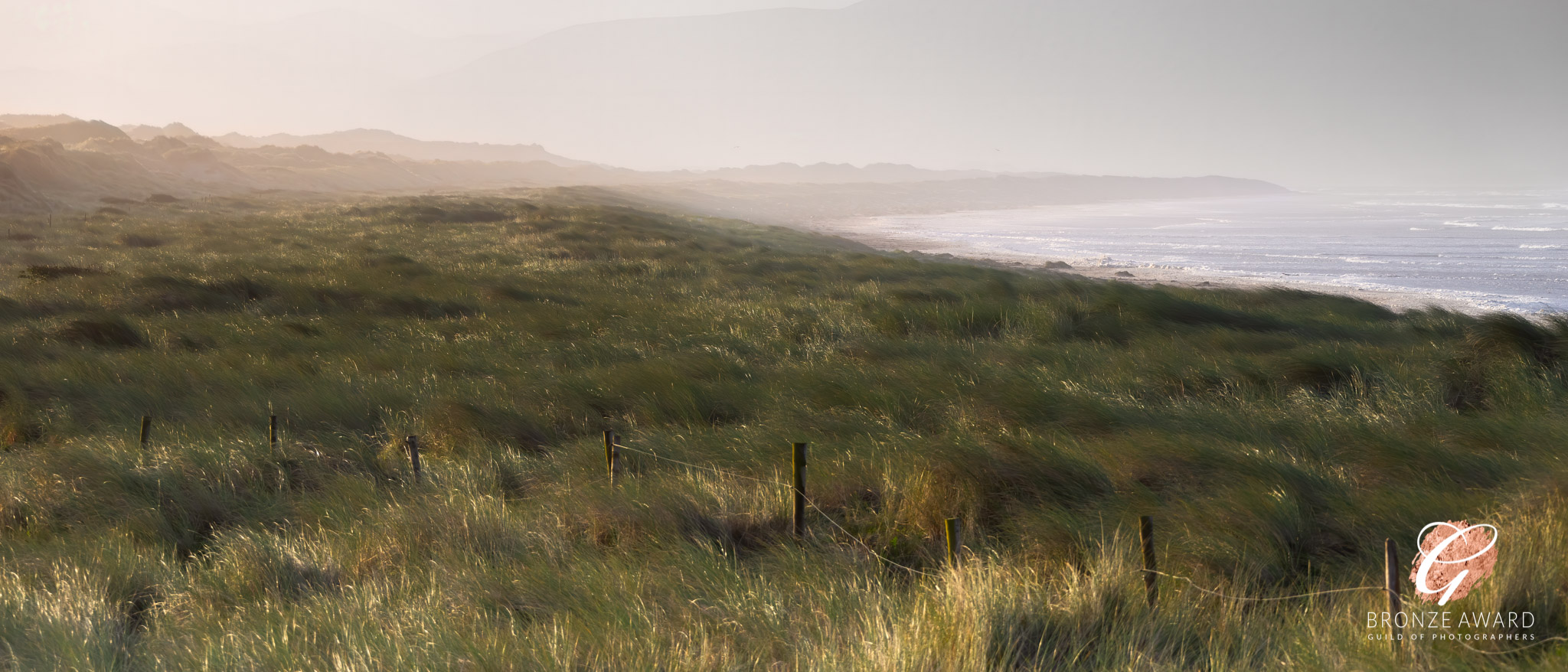 Dunes, sea and beach as dawn rises the morning after a storm on Inch Strand, County Kerry