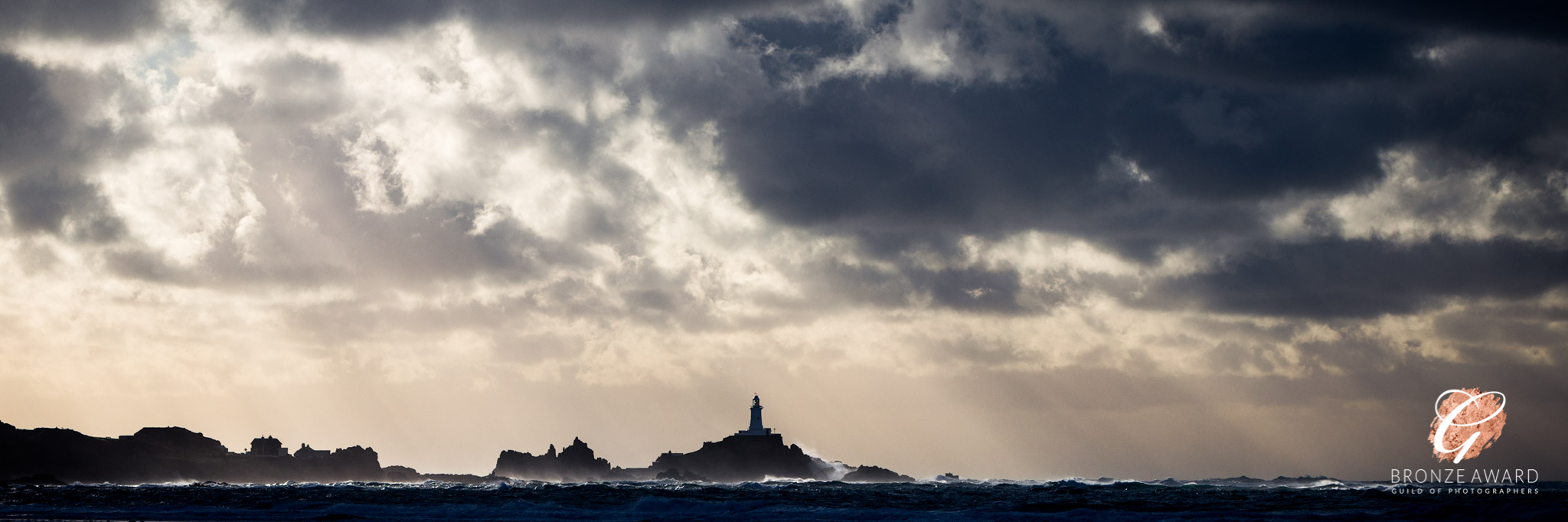 A seascape with dramatic sky taken from St Ouen's Bay and showing Corbiére Lighthouse