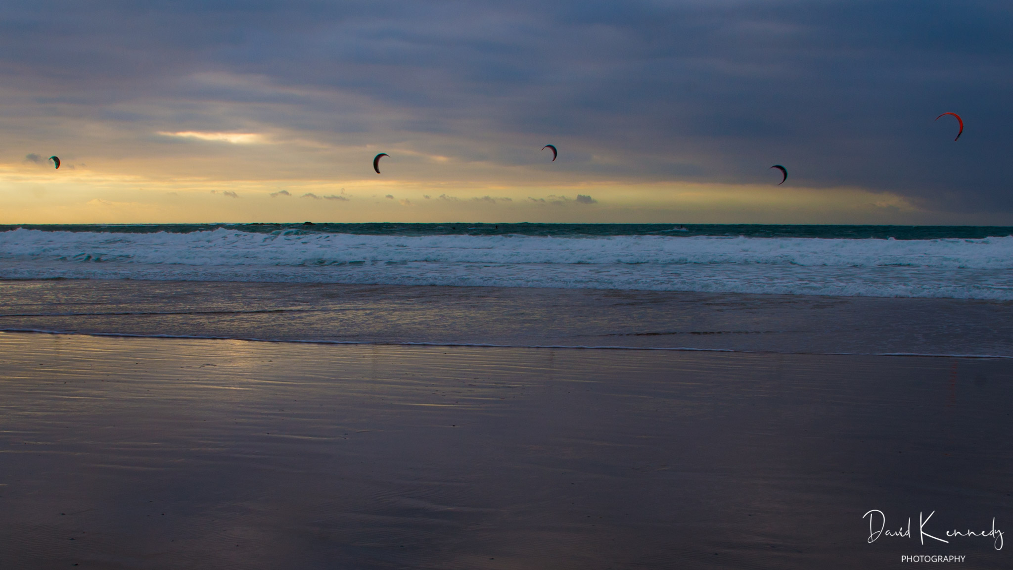 Beach and sky at sunset with five para surfers in action