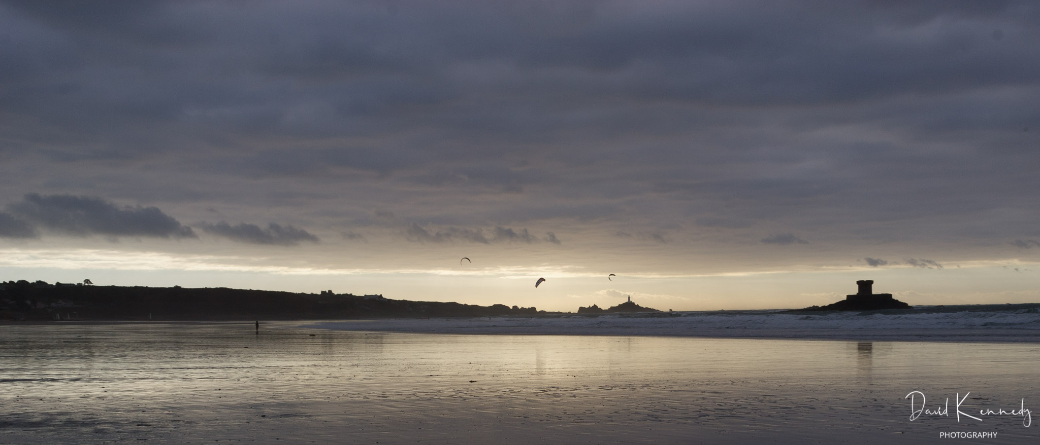 Para Surfers on St Ouen's Bay with backdrop of early sunset, lighthouse and defence tower