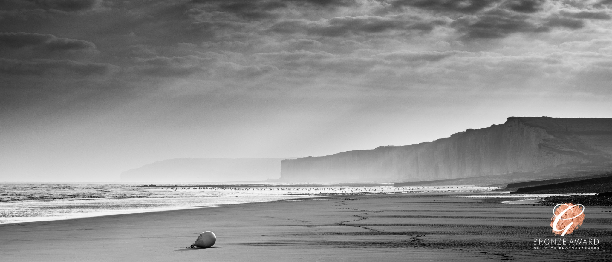 A black and white image of cliffs, dramatic sky and sea spray, taken from the beach.