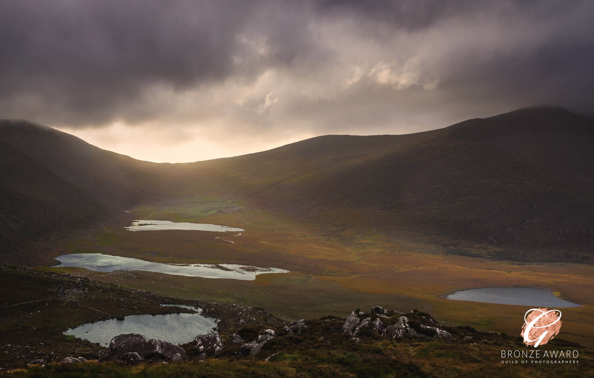 Dramatic sky and valley view over Conor Pass with autumnal colours and Lough Gal, Clogharee Lough, and Lough Atlea visible in the valley.