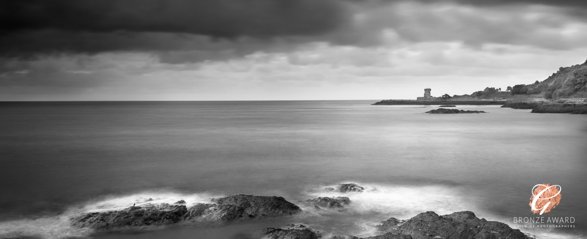 A black and white image of sea with Archirondel Tower on the horizon and rocks in the foreground and a dramatic sky.