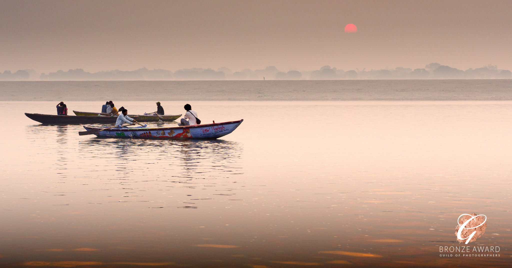 Looking over the Ganges towards the red-orange rising Sun, with rowing boats in the foreground.