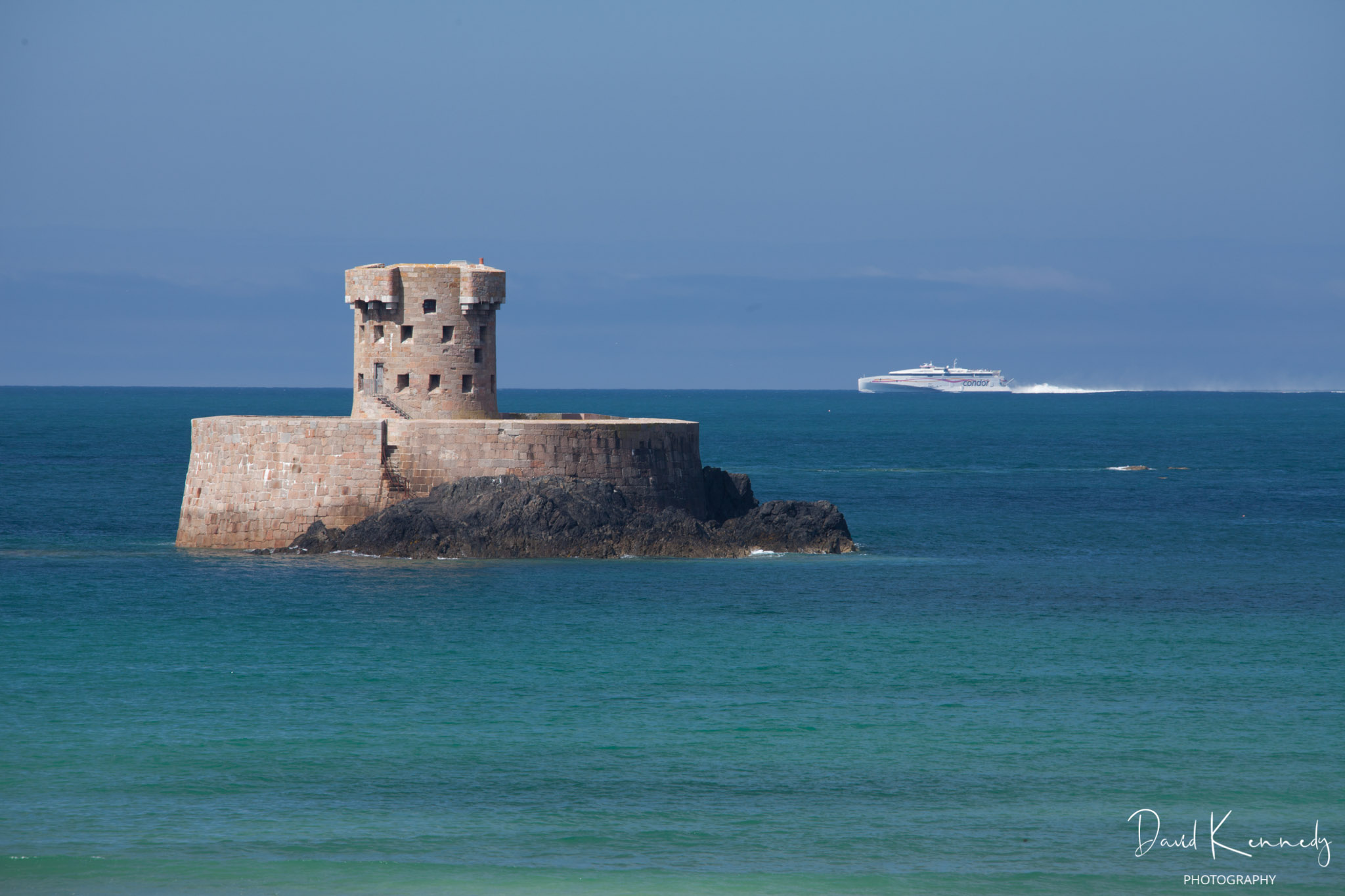 The fast ferry from Poole passing behind Le Rocco Tower and St Ouen's on the way to Jersey