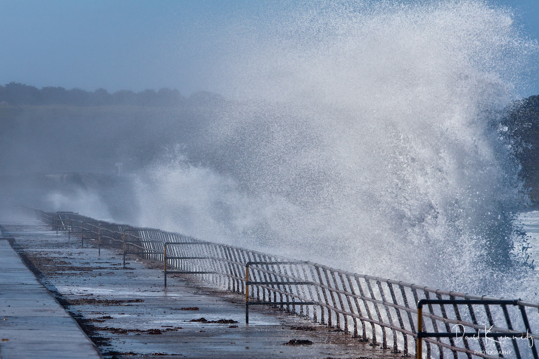 A wave breaking over the sea wall and spraying into the air over a barrier