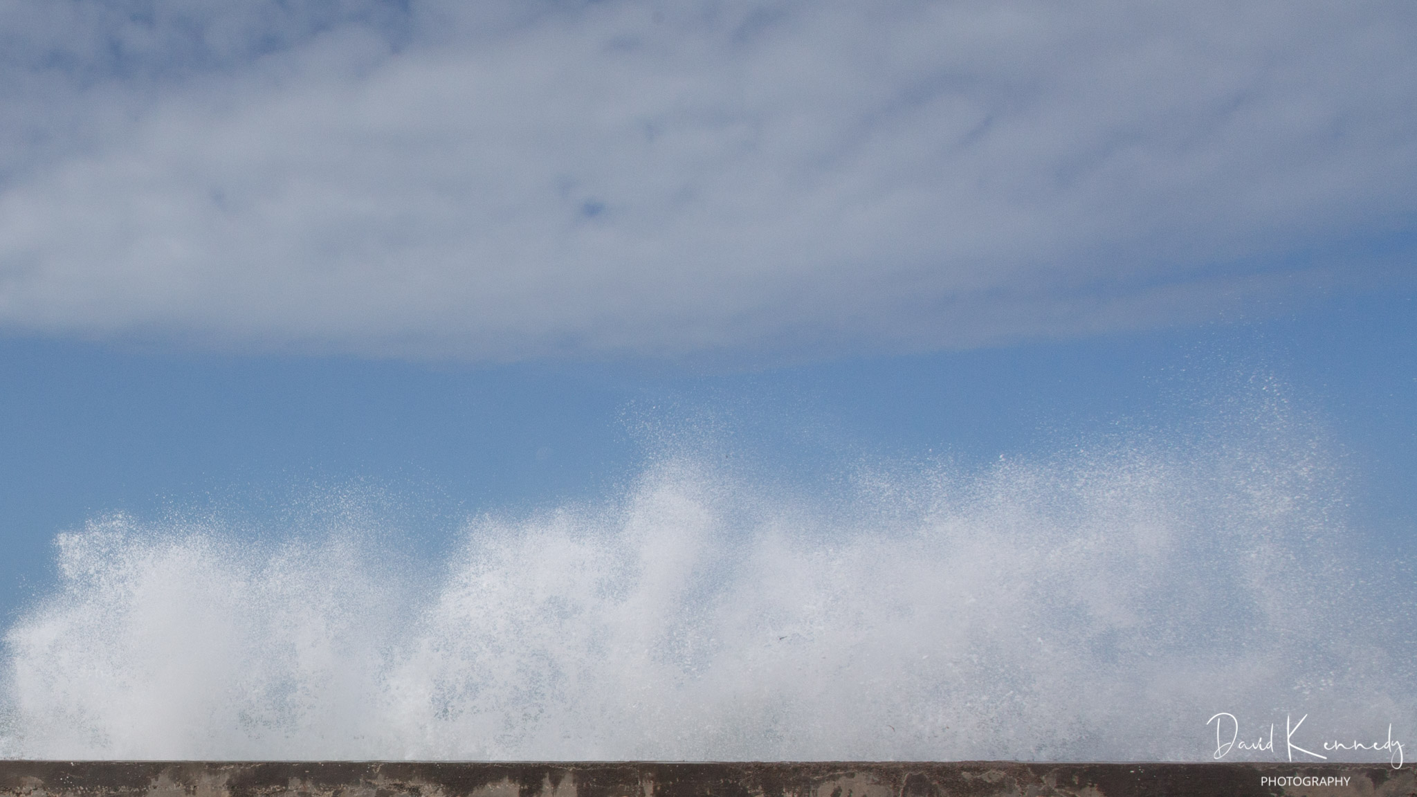 A white cloud in a blue sky above the spray from a breaker rising above the sea wall