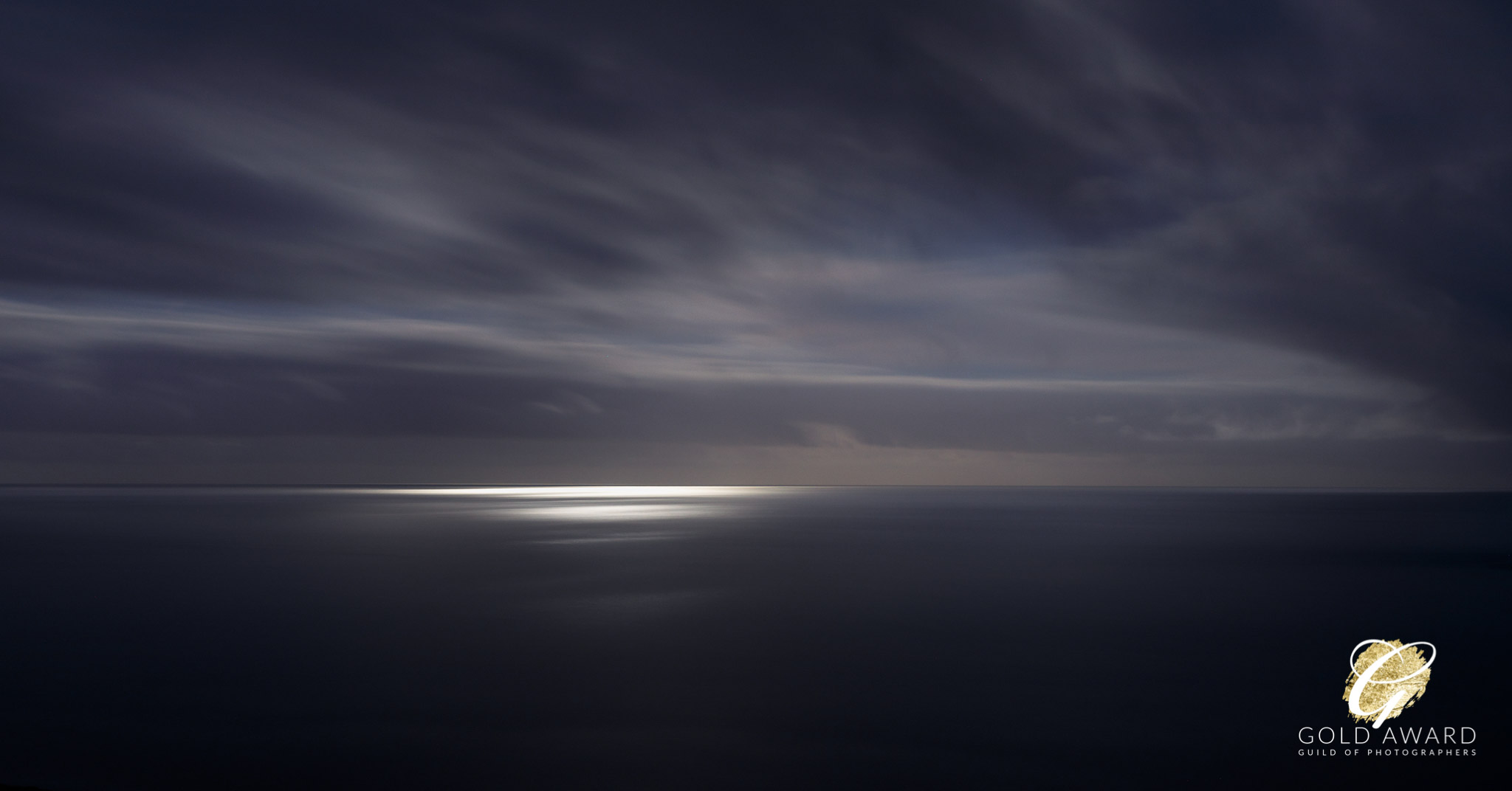 Moonlit view over the Atlantic Ocean from West Cork with a calm sea and dramatic soft sky.