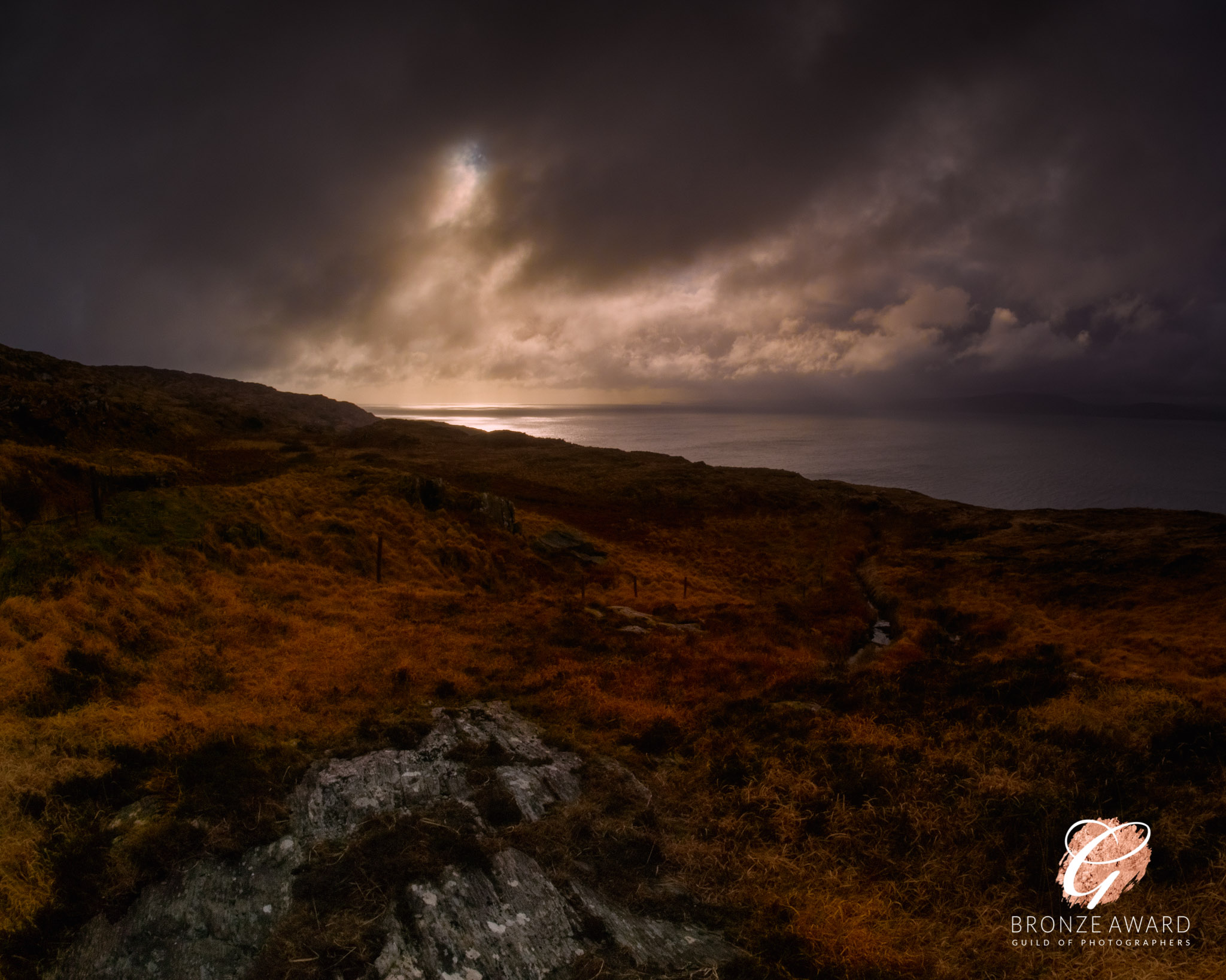 An autumnal view along the Wild Atlantic Way looking out over orange-brown bracken towards the Atlantic