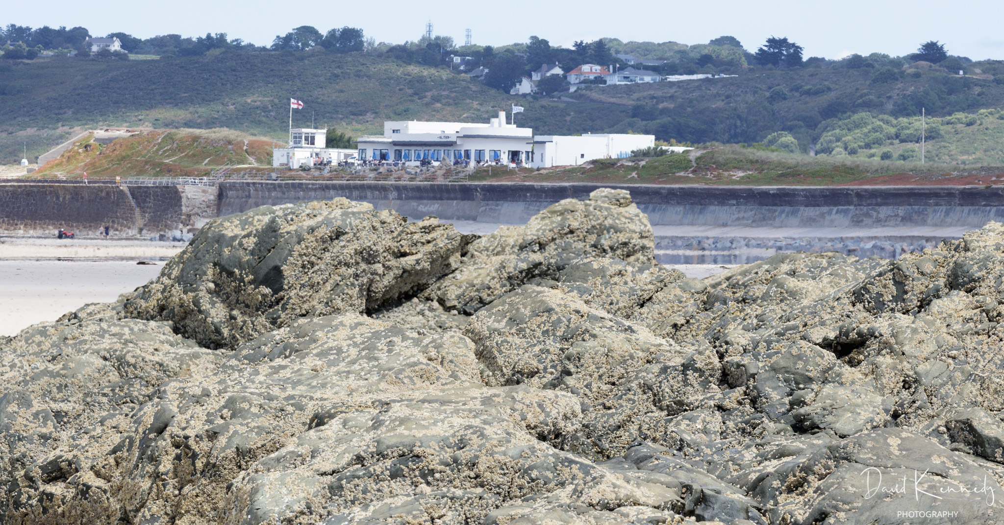 View over a foreground rock, with the sea wall and a large café restaurant above.