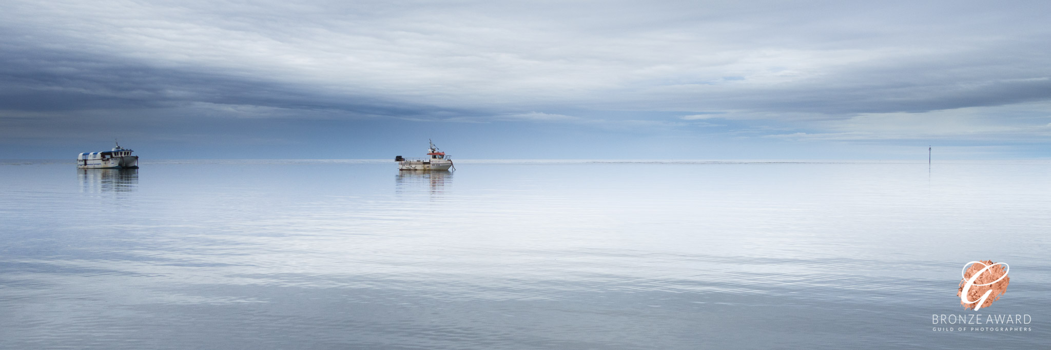 A calm sea reflecting a light but dramatic sky, with fishing boats moored to one side.