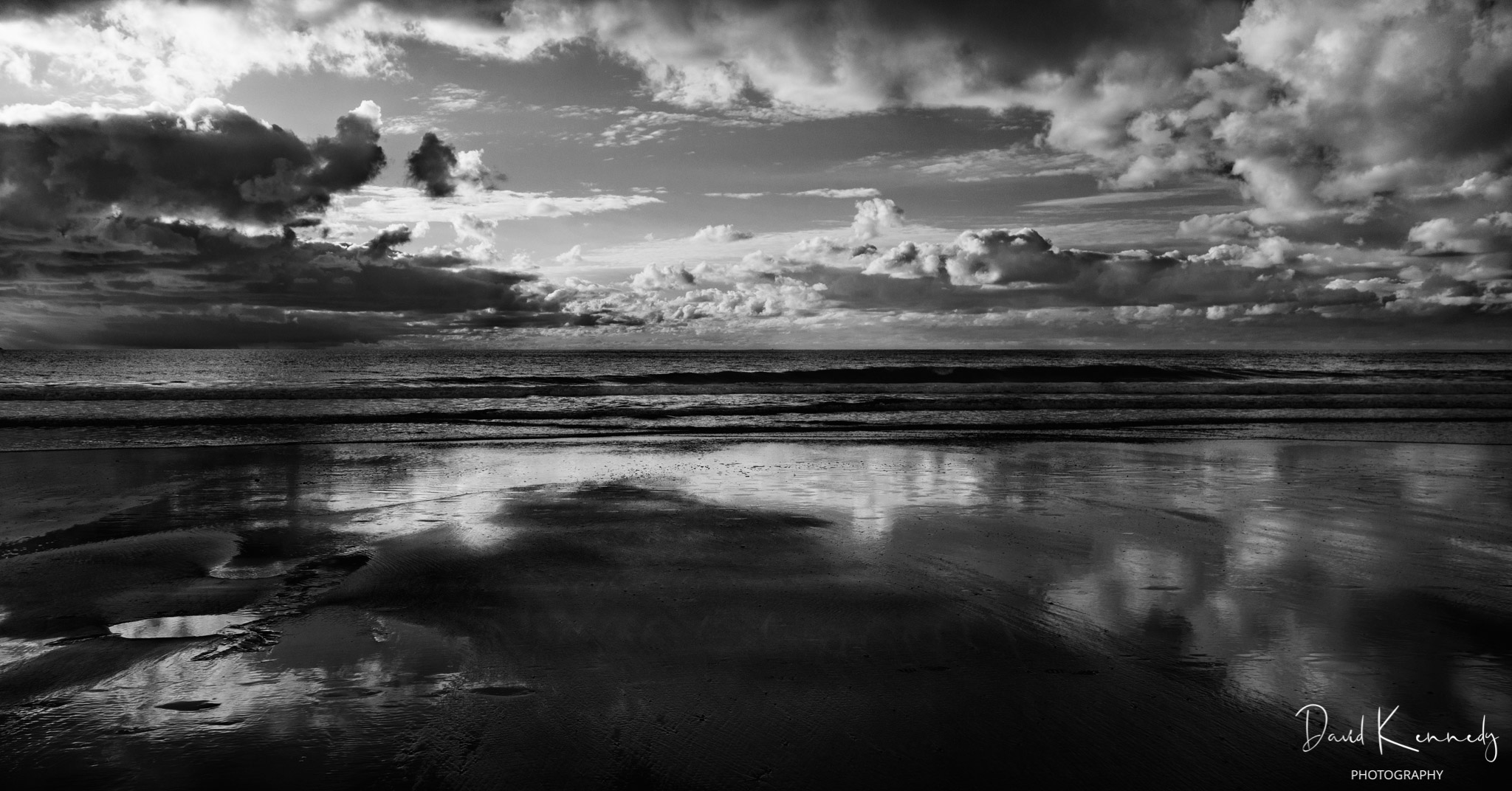 Looking out towards the shoreline with a dramatic sky reflected on the wet beach in the foreground
