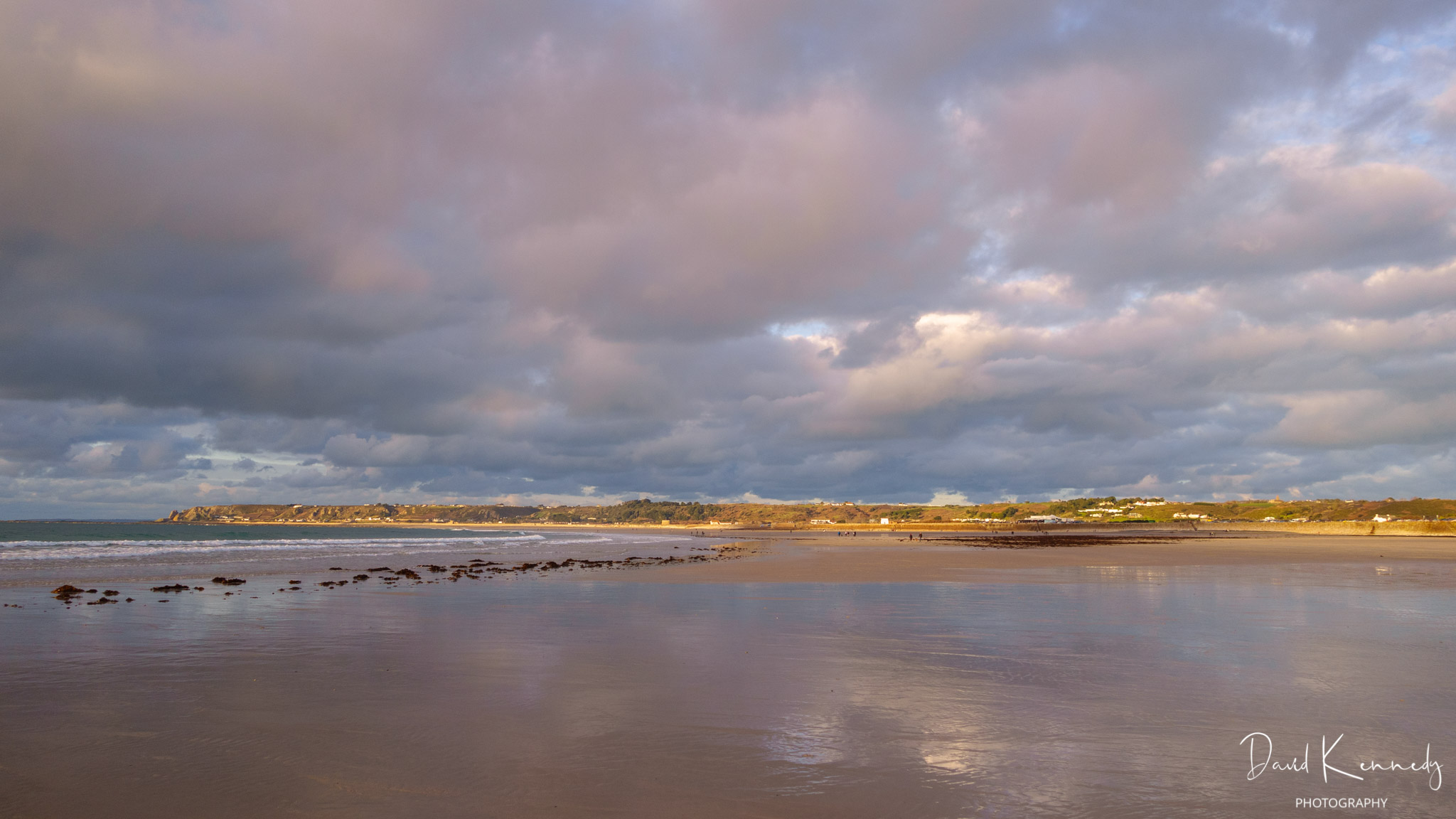 A wide view of St Ouen's beach looking north with the cloudy sky, tinged with orange, reflected on the wet sand