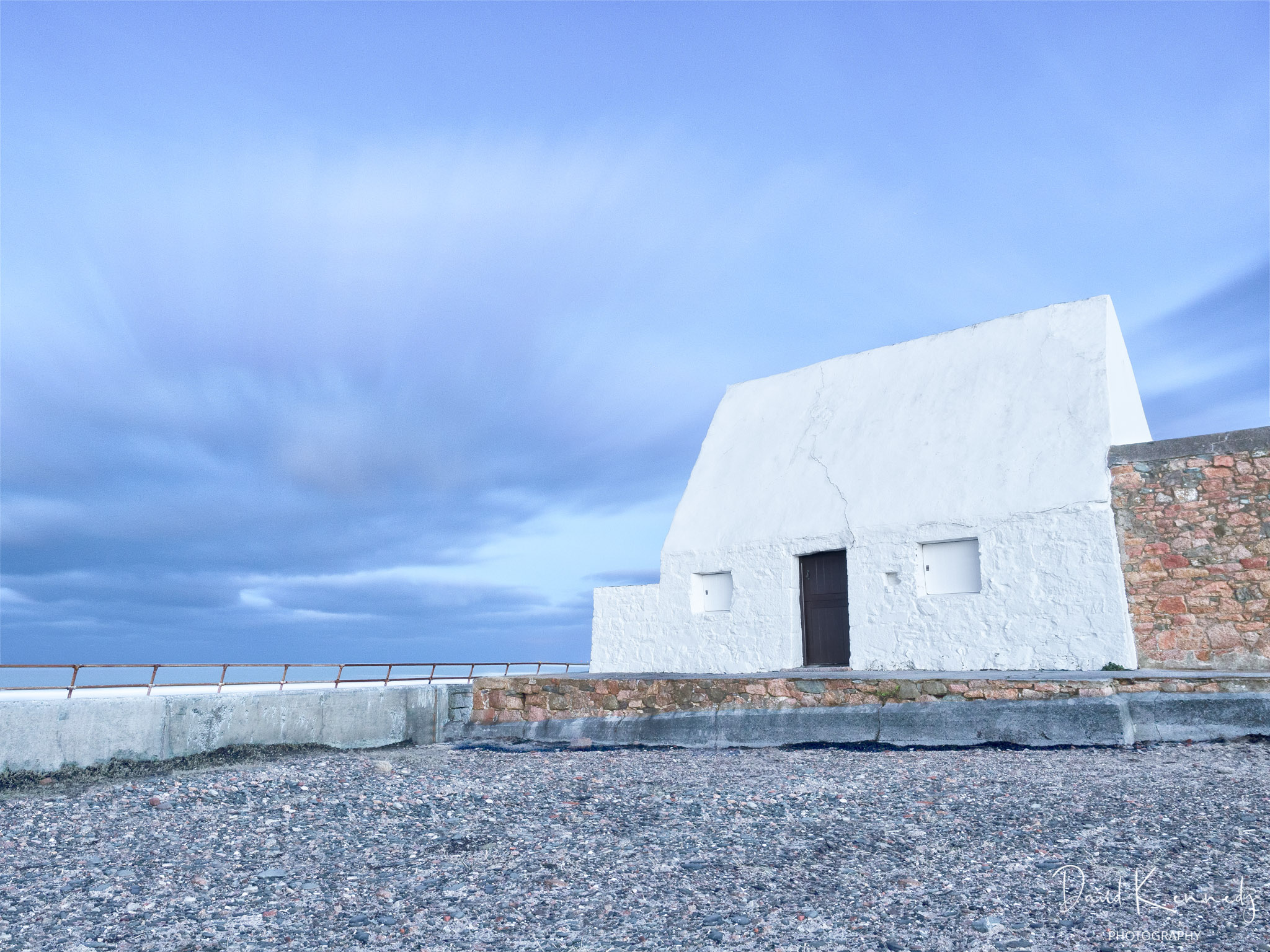 Ancient cottage painted entirely white with dramatic sky