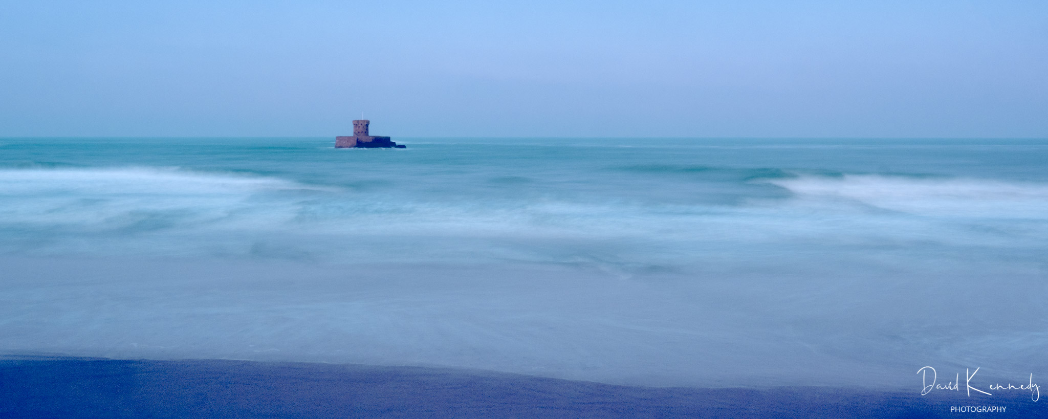 La Rocco Tower built in Napoleonic Times, at high tide in St Ouen's Bay Jersey Channel Islands