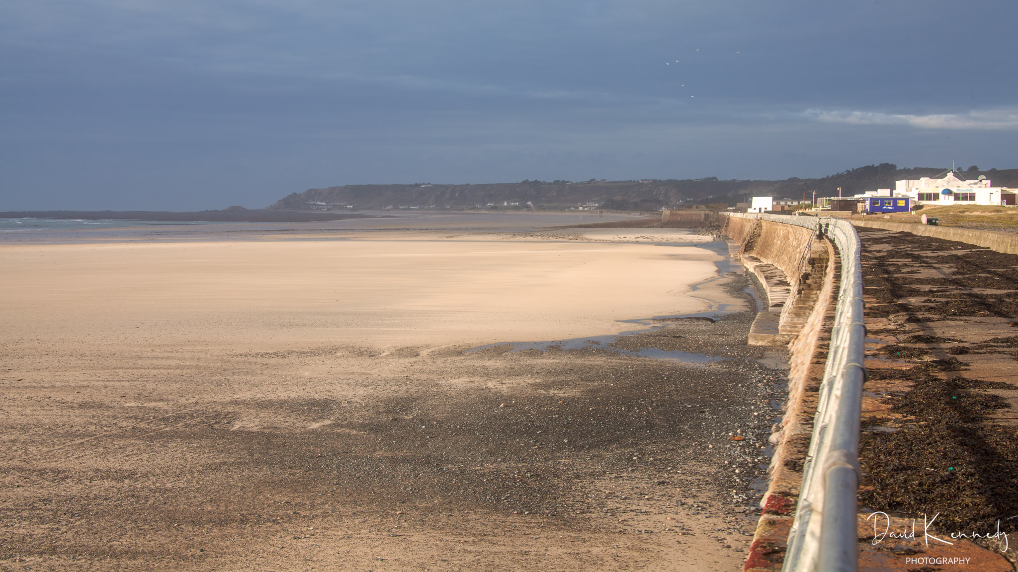 View along the sea wall on St Ouen's Bay, Jersey, showing wide sandy beach