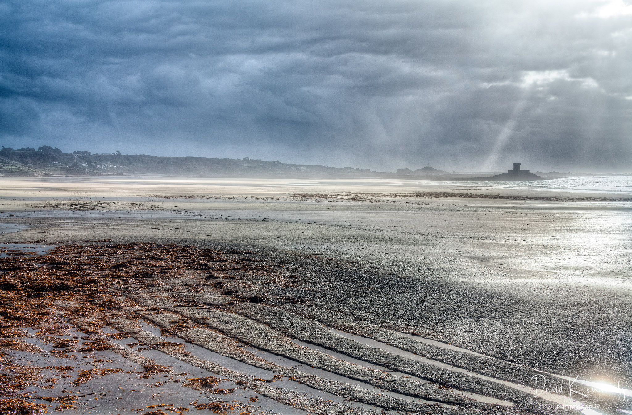 Wide view of an expanse of beach and moody sky