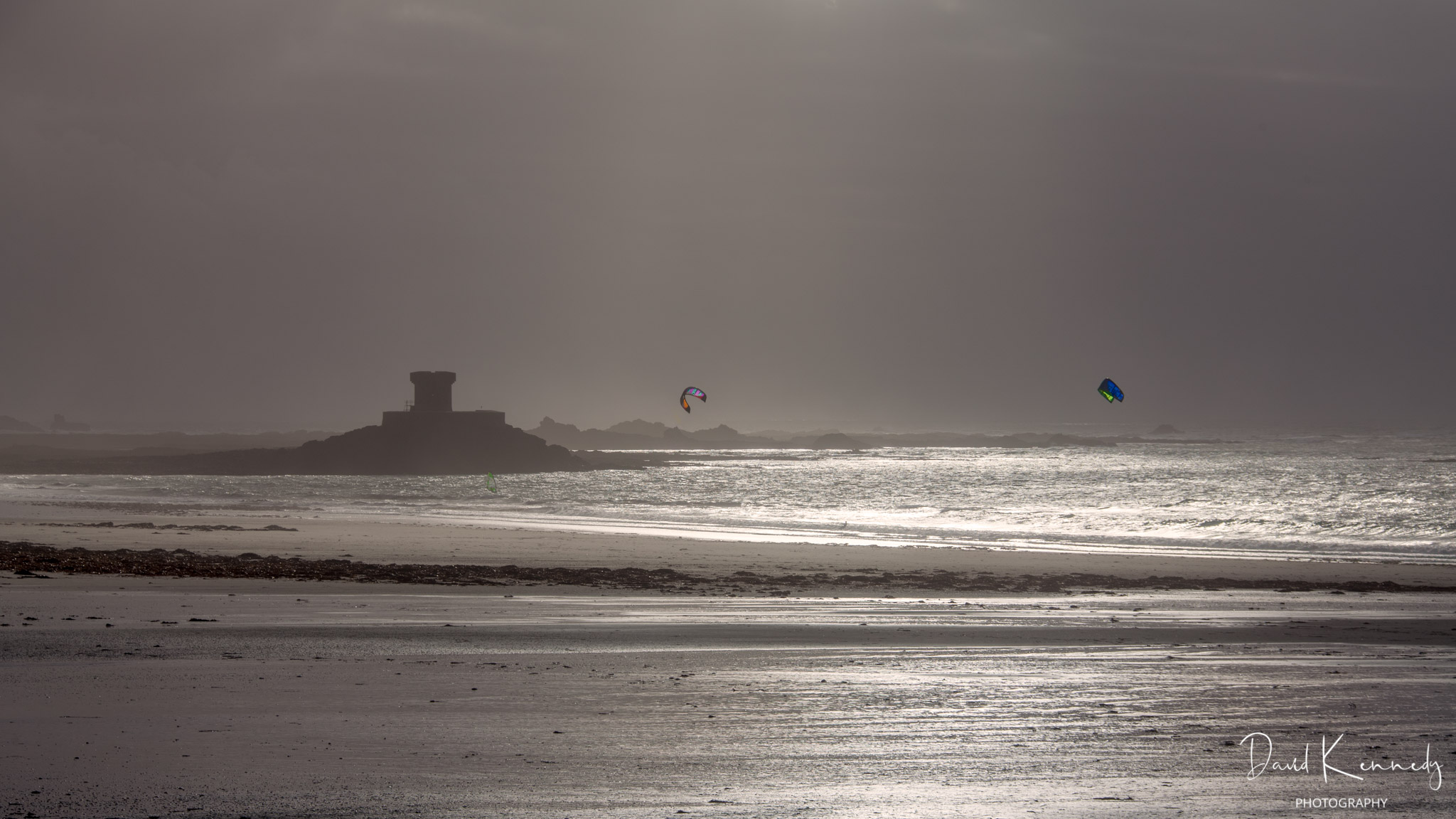 A view over the sea towards a Napoleonic era defence tower, with two para surfers and a windsurfer in view