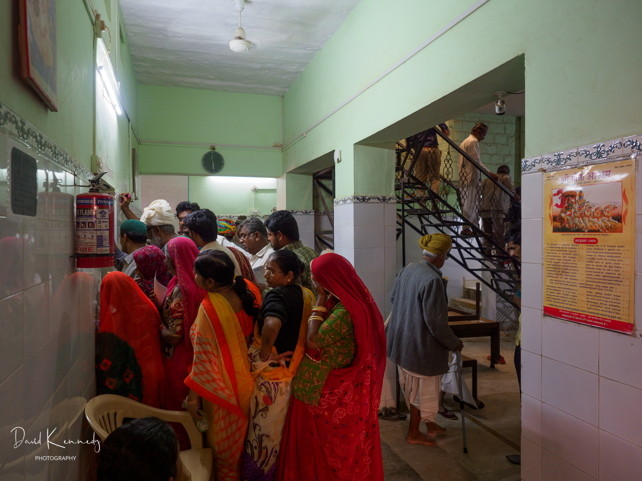 A group of people waiting outside a treatment room in an eye clinic, India