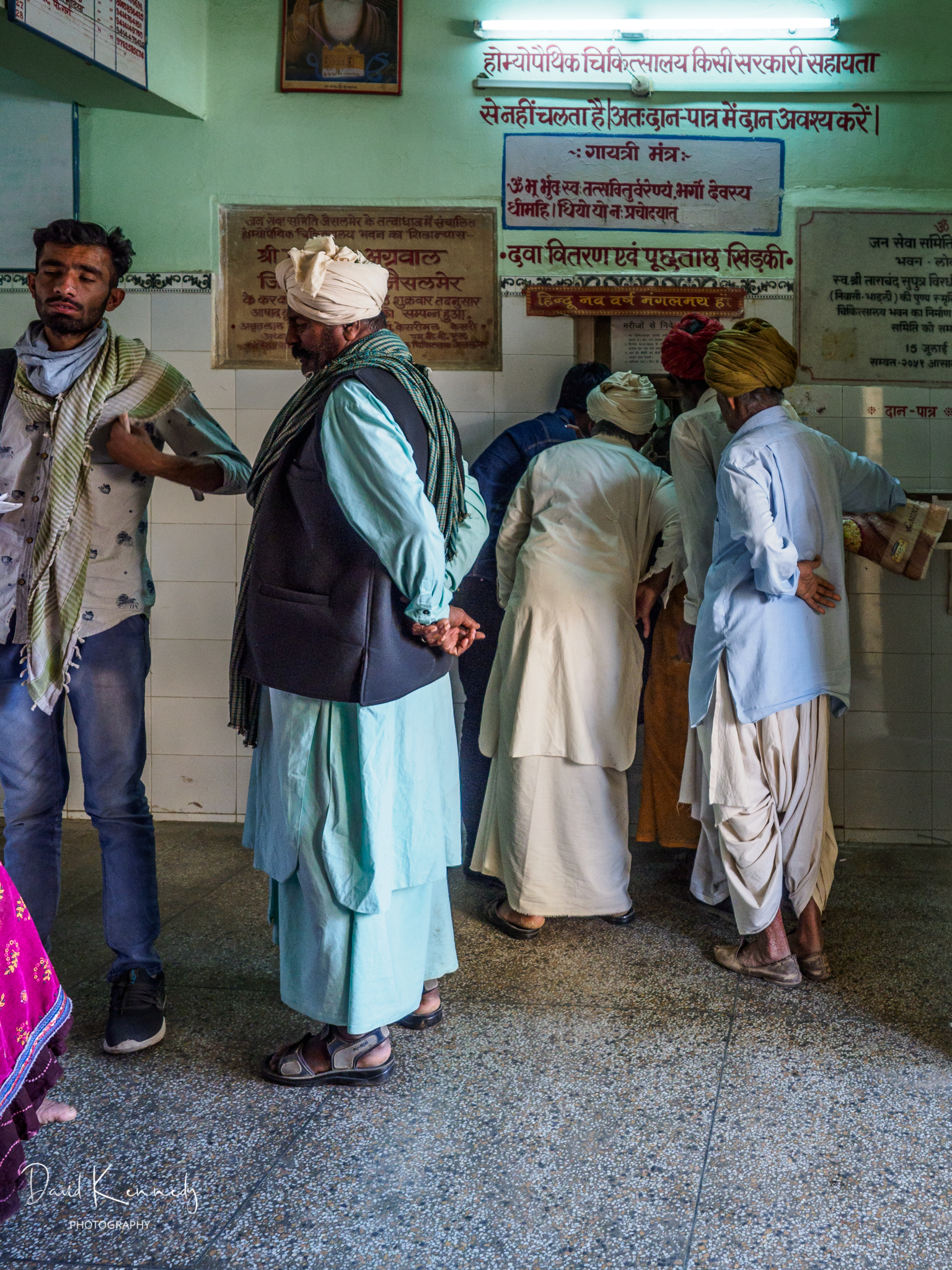 Men standing at reception window in eye clinic in India
