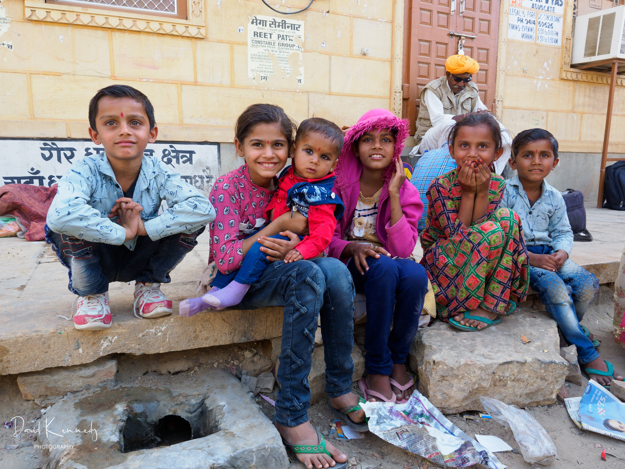 A group of happy children sat at the side of the road, Jaisalmer, India