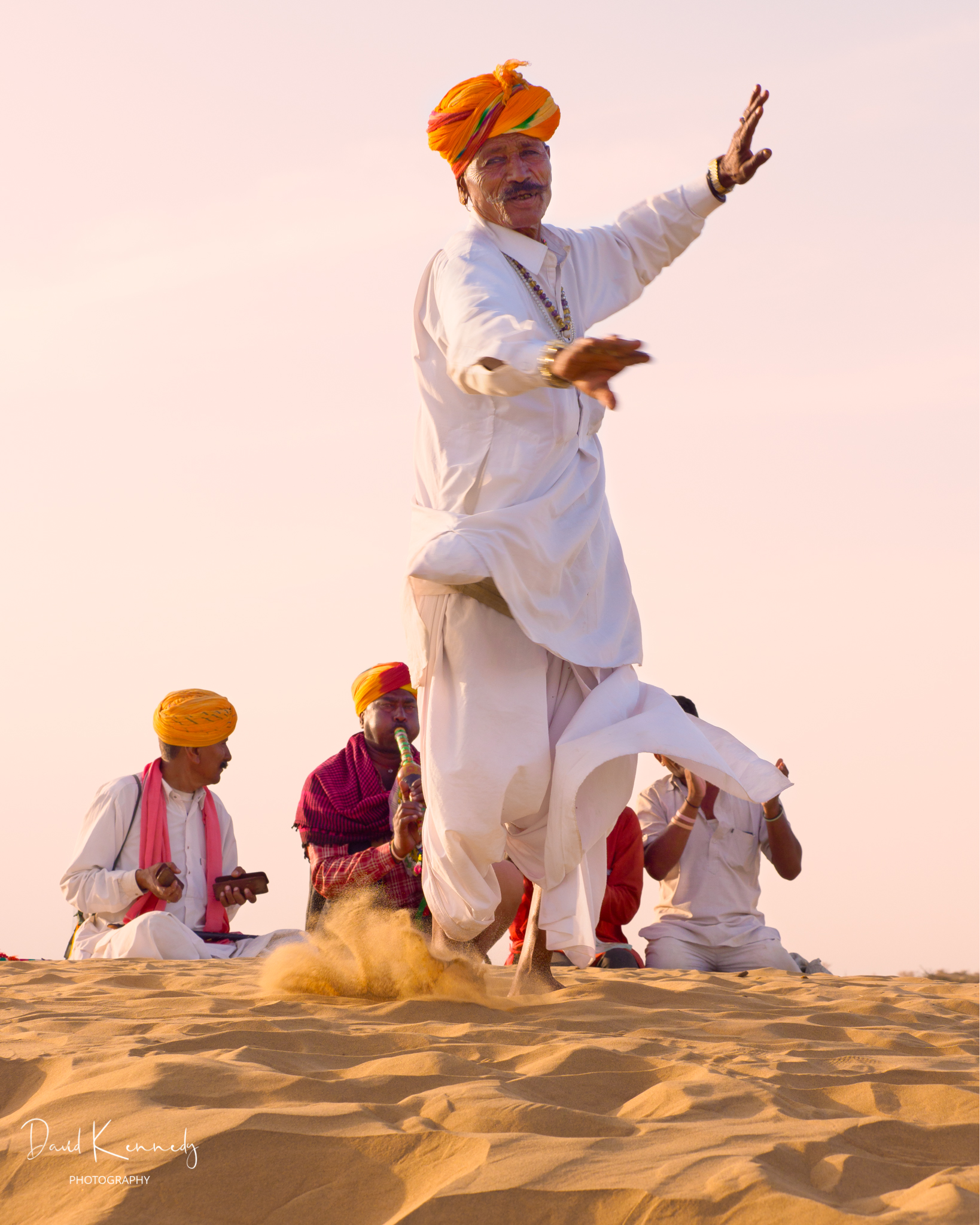 Man dancing to musicians in the desert