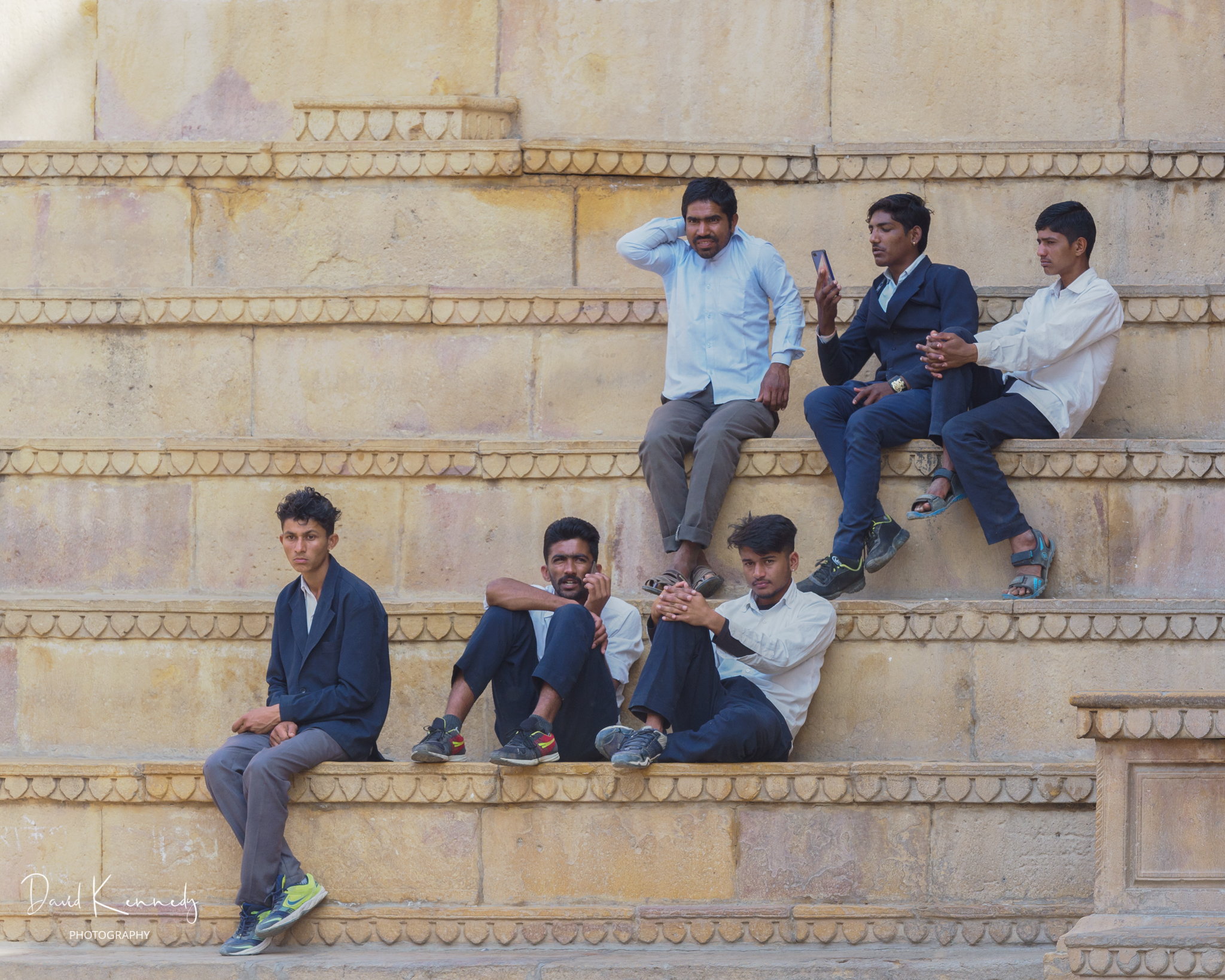 Group of smartly dressed young men watching the world go by in India